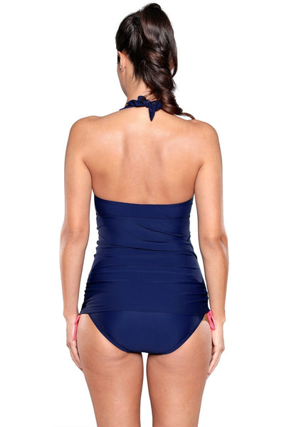 Back view of model wearing navy contrast pink-trim halter swimsuit