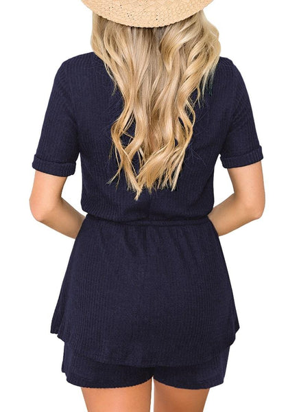 Back view of model wearing navy crew neck overlay drawstring knit romper