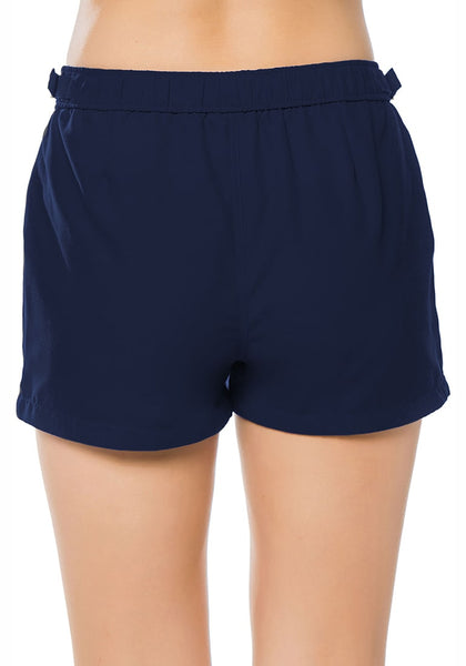 Back view of model wearing navy elastic waist buckle sides swim board shorts