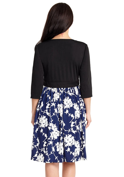Back view of model wearing navy floral pattern surplice skater dress