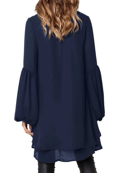 Back view of model wearing navy long lantern sleeves layered high-low blouse