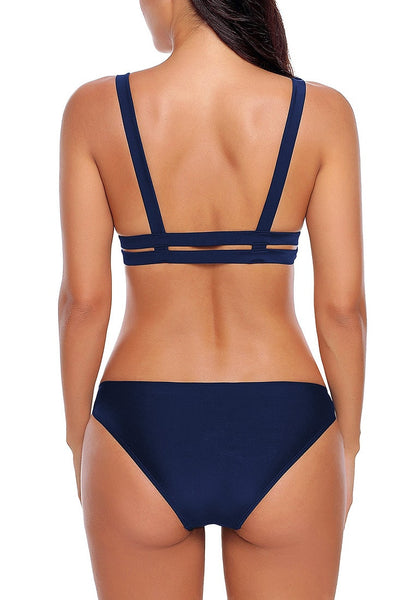Back view of model wearing navy strappy triangle bikini set