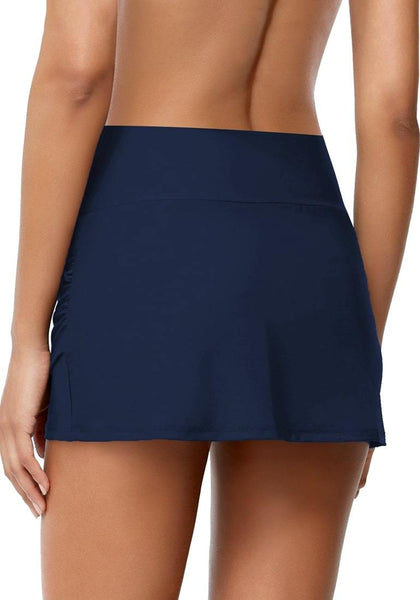 Back view of model wearing navy tulip-hem mid-waist ruched swim skirt