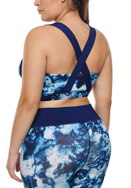 Back view of model wearing plus size blue abstract print crisscross-back sports bra