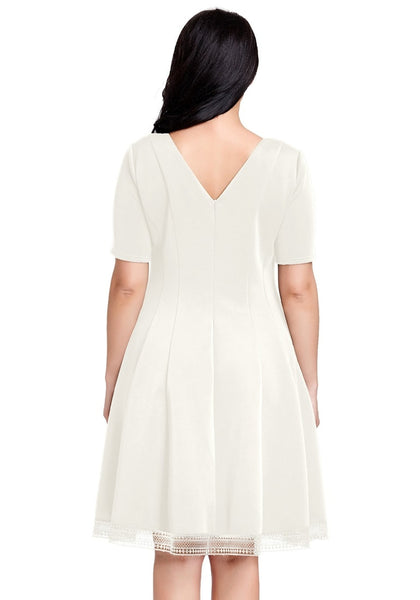 Back view of model wearing plus size off white short-sleeves skater dress