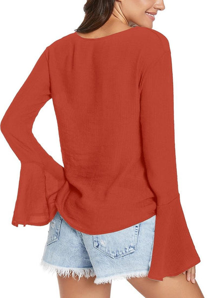Back view of model wearing rust V-neck trumpet sleeves tie-front blouse