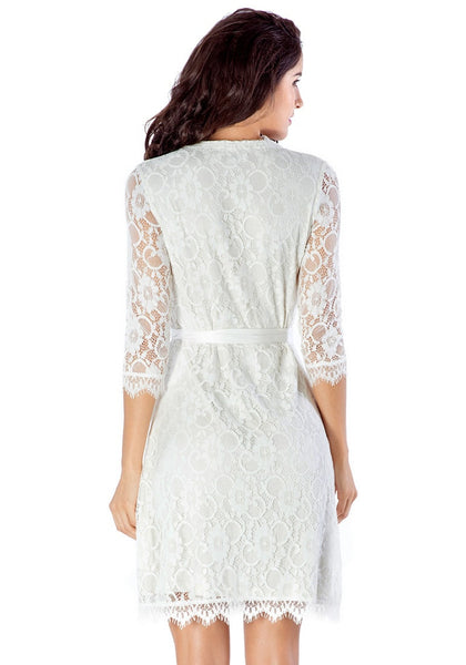Back view of model wearing white lace overlay plunge wrap-style dress