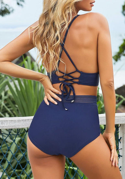 Back view of pretty model wearing navy blue elastic panel high-waist swim bottom with her triangle top