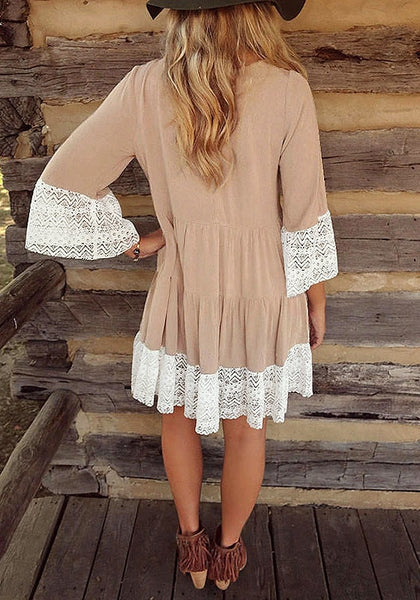 Back view of woman in khaki lace-trim pleated loose-fit dress