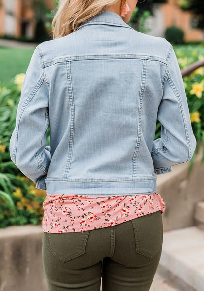 Back view of model wearing light blue button down women's denim jacket