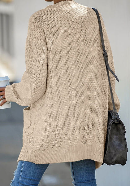 Back view of model wearing beige open-front oversized cable knit cardigan