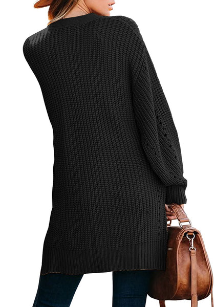 Back view of model wearing black open-front side slit oversized cable knit cardigan