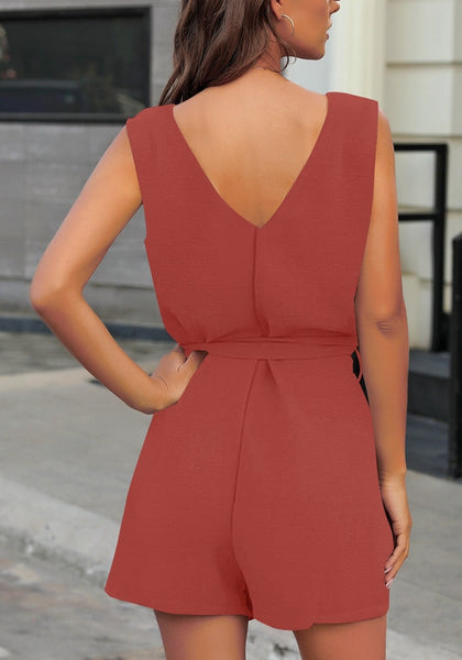 Back view of model wearing coral pink V-neck sleeveless belted button-up romper