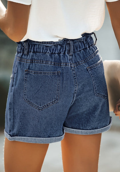 Back view of model wearing dark blue elastic-waist button front roll-over denim shorts