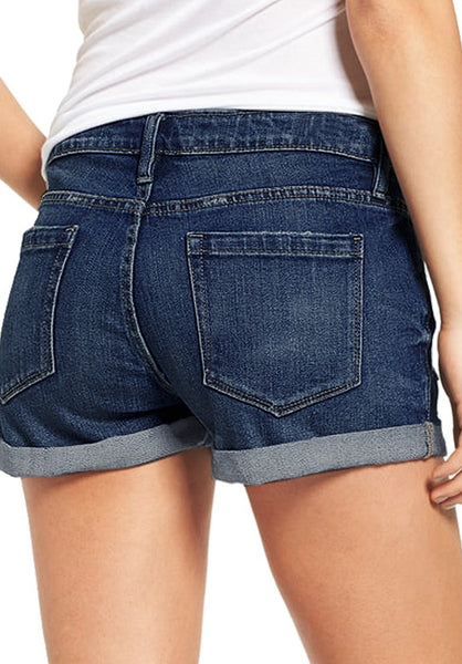 Back view of model wearing dark blue roll-over hem button-up distressed denim shorts
