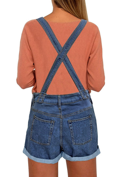Back view of model wearing dark blue rolled hem ripped shorts denim bib overall