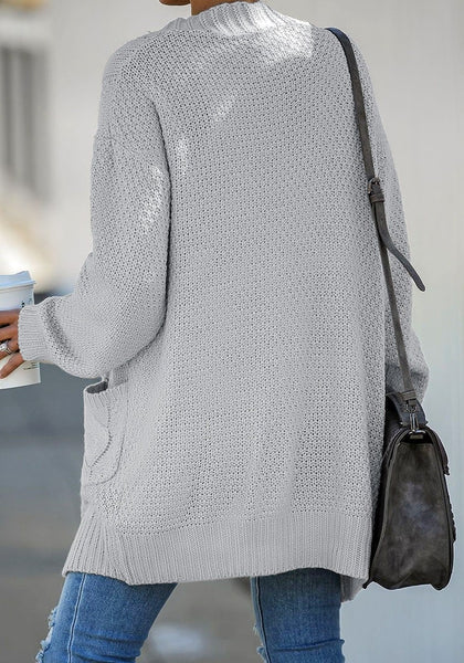 Back view of model wearing grey open-front oversized cable knit cardigan