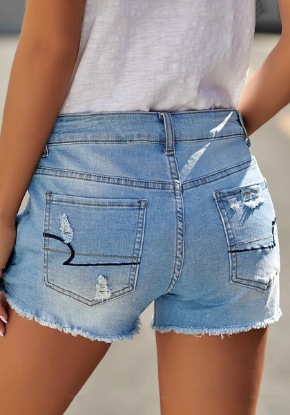 Back view of model wearing light blue raw hem distressed faded denim shorts