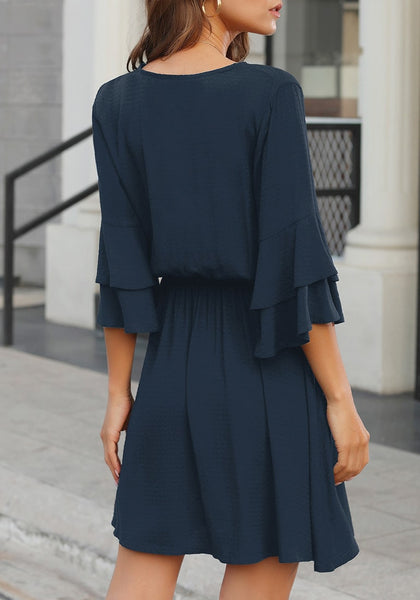 Back view of model wearing navy V-neckline elastic waist layered bell sleeves dress