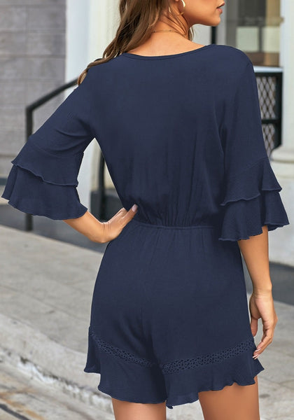 Back view of model wearing navy ruffle 34 sleeves elastic-waist button loop romper