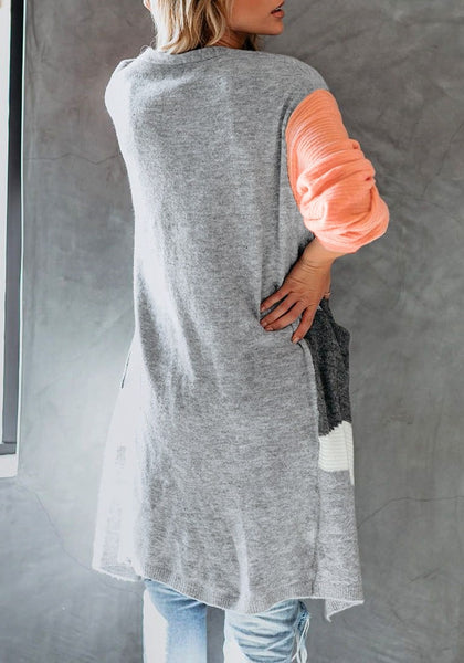Back view of model wearing orange open-front colorblock oversized long knit cardigan