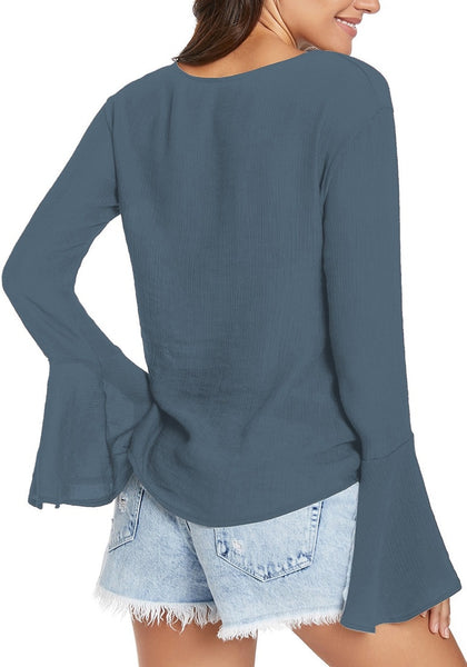 Back view of model wearing stone blue V-neckline trumpet sleeves tie-front blouse