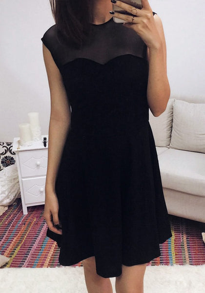 Beautiful girl in black illusion-neck sleeveless mini dress