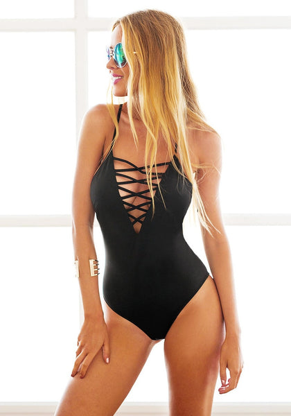 Blonde model wears black lace-up swimsuit