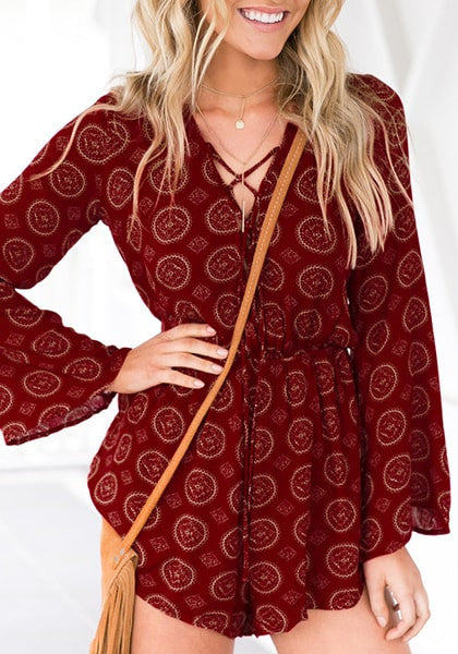 Blonde woman poses in maroon lace-up trumpet sleeves romper with one hand on hip