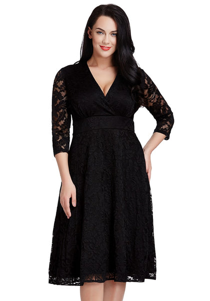 Brunette lady poses in black lace surplice midi dress and one hand on hip