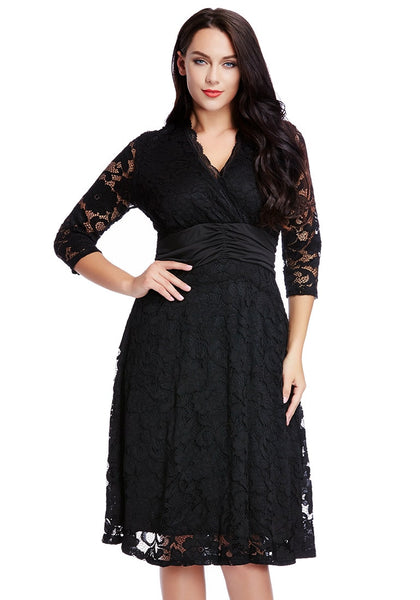 Brunette model in black lace surplice ruched-waist dress with one hand on hip