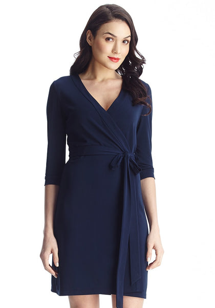 Brunette model looking radiant in navy plunge wrap-style belted dress
