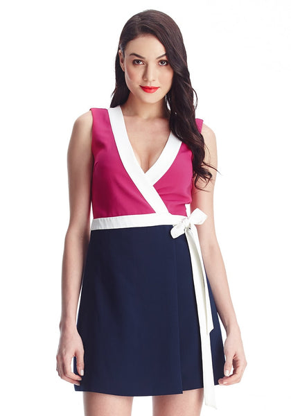 Brunette model wearing pink and navy sleeveless wrap-style dress