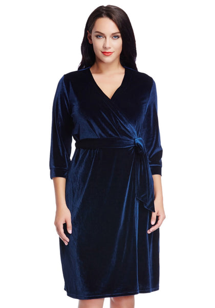 Brunette model wearing plus size navy blue velvet wrap dress