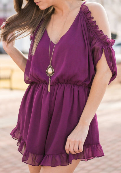 Brunette model wearing purple cold-shoulder ruffled romper