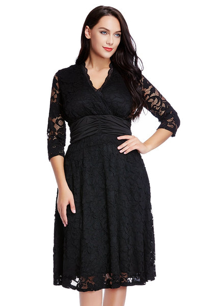 Brunette woman in black lace surplice ruched-waist dress with one hand on hip