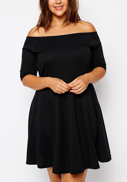 Brunette woman in black off-shoulder skater dress