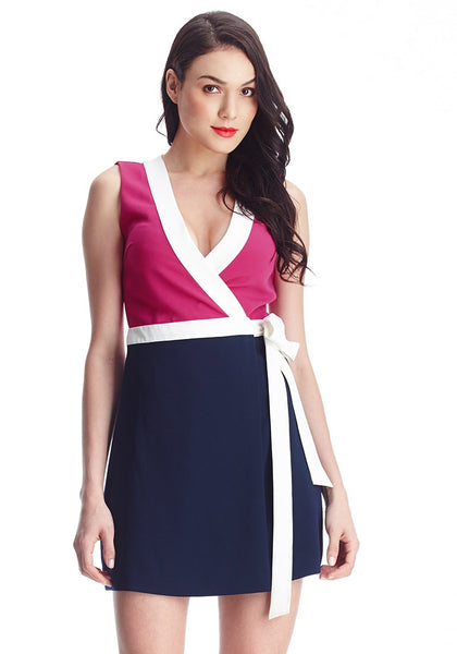 Brunette woman models pink and navy sleeveless wrap-style dress