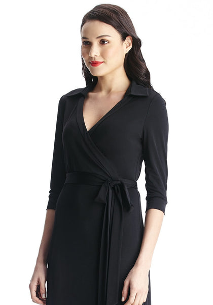 Close-up left side view of model in black plunge wrap belted maxi dress