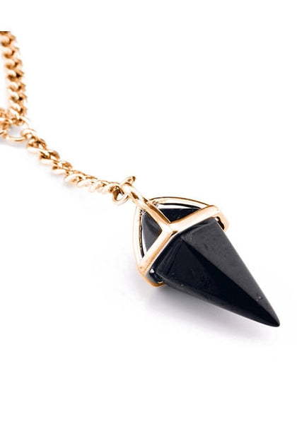 Close-up of black charm layered Y necklace's crystal pendant