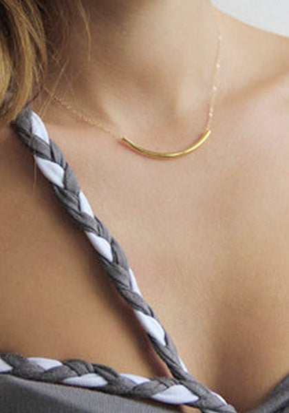 Close-up of model wearing gold curved bar necklace