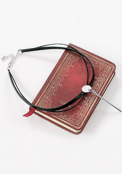 Close-up shot of black layered PU silver bar choker on top of a red book