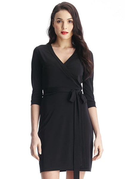 Close-up shot of brunette woman in black plunge wrap-style belted dress