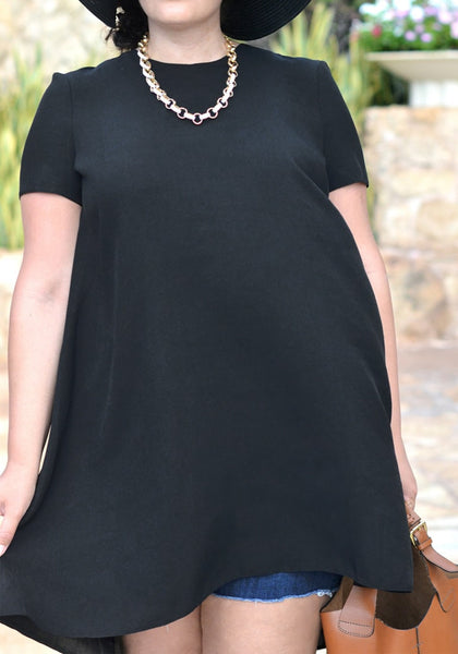 Close-up shot of curvy woman in black hi-lo trapeze tunic