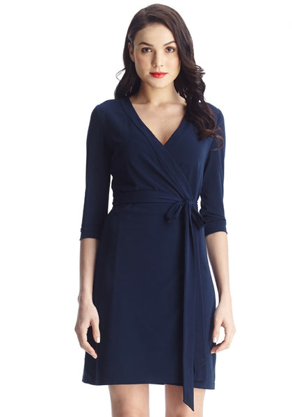 Close-up shot of lady in navy plunge wrap-style belted dress