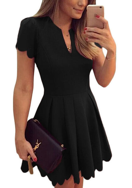 Close up angled view of model in black scallop hem skater dress
