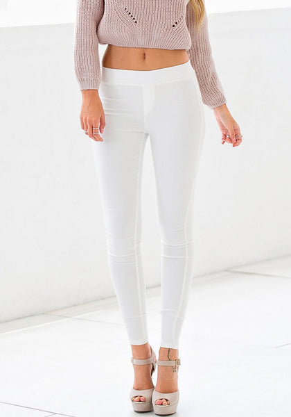 Close up of model in white skinny high-waisted pants