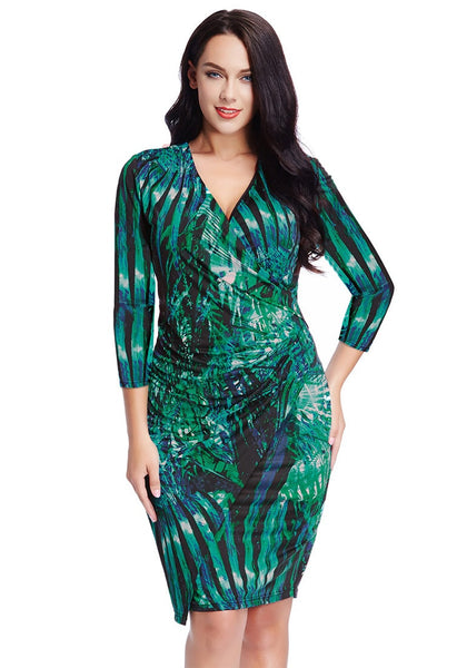 Model poses with one hand on the waist wearing plus size green leaf-printed midi wrap dress