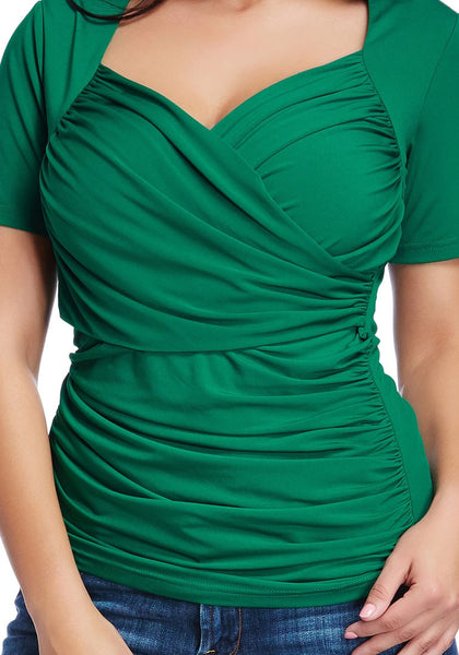 Close up shot of model in plus size green ruched surplice top