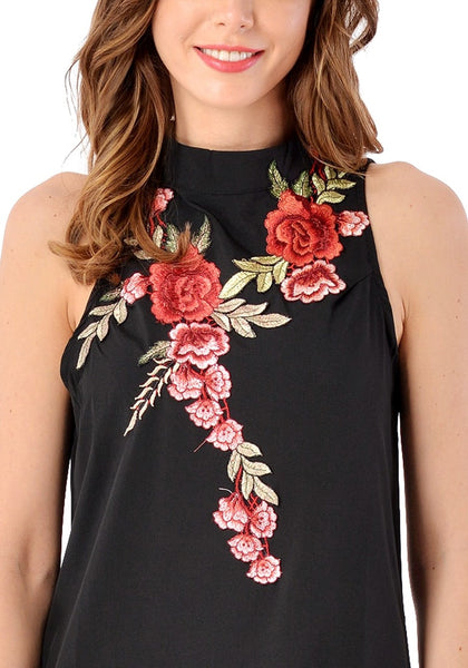 Close up shot of model wearing black mock neck floral embroidered dress